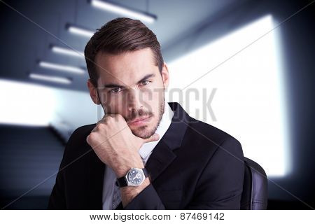Cheerful businessman posing with hand on chin against grey room