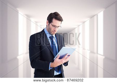 Businessman using a tablet computer against digitally generated room