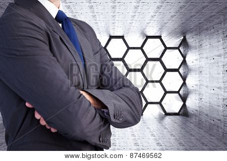 Man in a suit with folded arms against hexagon room