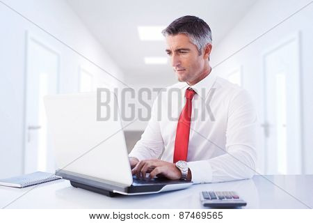 Businessman using laptop against bright hallway with several doors