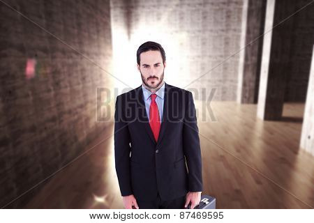 Serious handsome businessman holding briefcase against abstract room