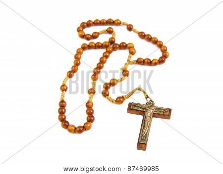 Wood rosary and cross with slightly unfocused beads isolated on a white background
