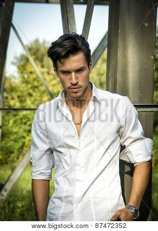 Handsome young man leaning against metal electricity trellis