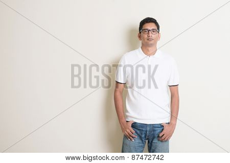 Portrait of cool Indian guy looking at camera, standing on plain background with shadow, copy space at side.