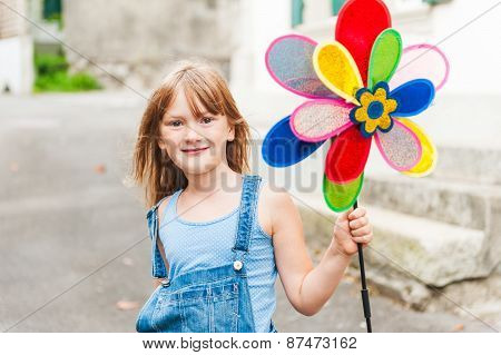 Cute little girl playing with pinwheel outdoors