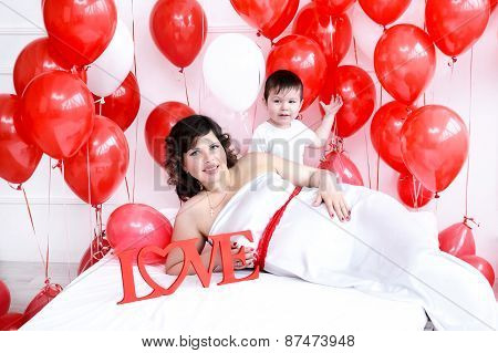 Young pregnant woman and her son laying on a bed with love sign and red balloons around