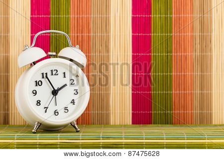 Table Clock At Coloured Decorative Background