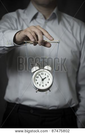 Business Man Holds A Clock, Hanging On Cords, And Manages It
