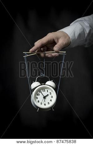 Hand Holds A Clock, Hanging On Cords, And Manages It
