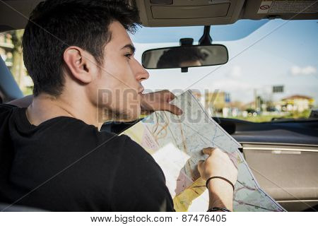 Gorgeous Young Man Inside Car Asking for Directions Holding a Map