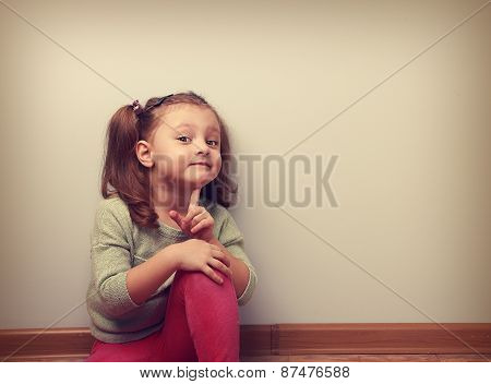 Dreaming Smiling Sitting Kid Girl Looking Fun With Finger Near Face