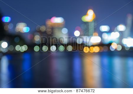 Blurred unfocused city view at night with water reflection