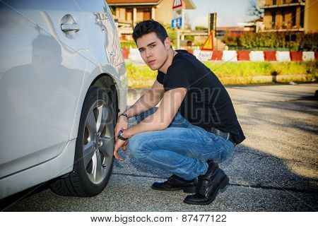 Handsome Man Sitting Besides the Wheel of Car Changing Tires