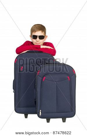 Portrait Of A Boy Wearing Sunglasses Sitting With Travel Bags