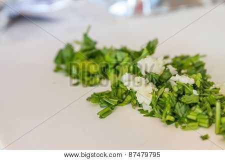 parsley and garlic on wooden cutting board, cooking time background