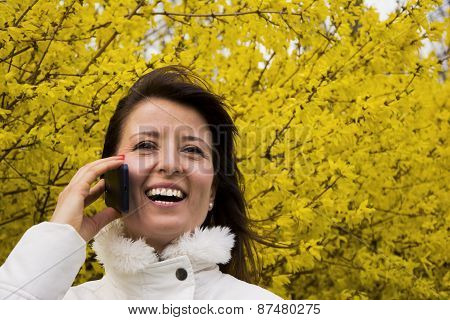 Young Woman Talking On The Phone In Outdoors