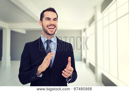 Happy businessman standing and clapping against modern white room with window