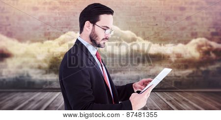 Businessman scrolling on his digital tablet against clouds in a room