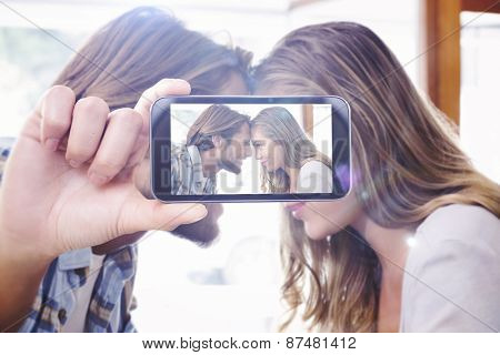 Hand holding smartphone showing against happy couple touching their heads