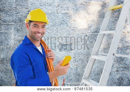 Smiling male electrician holding multimeter in office against grey