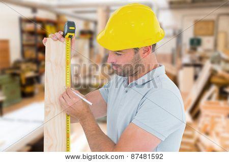 Carpenter using measure tape to mark on wooden plank against workshop