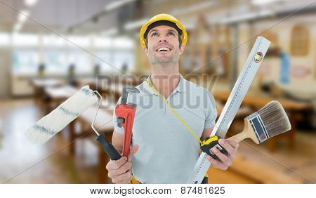 Worker holding various equipment over white background against workshop