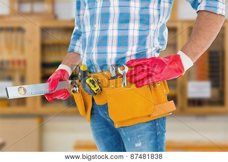 Midsection of handyman holding spirit level against workshop