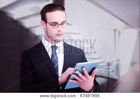 Unsmiling businessman using tablet pc against stylish modern home interior with staircase