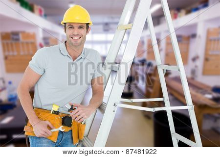 Worker holding tools while leaning on step ladder against workshop