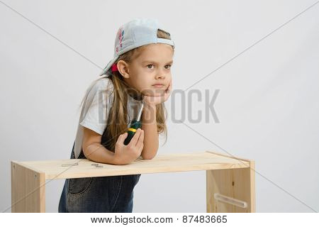 Girl-collector Of Furniture With A Screwdriver Thoughtfully Leaned Her Head