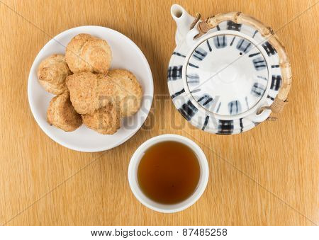 Porcelain Teapot, Cup Of Tea And Biscuits On  Saucer Isolated On Table