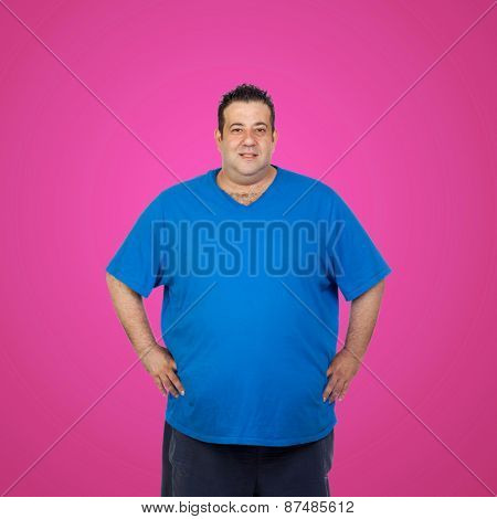 Happy fat man with blue shirt and a pink background