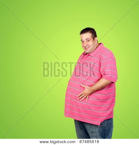 Happy fat man with blue shirt and a green background