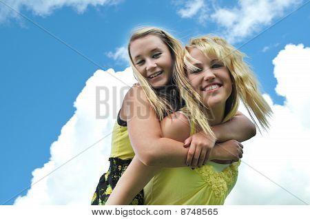 Girl Friends Piggyback Ride In Sunshine