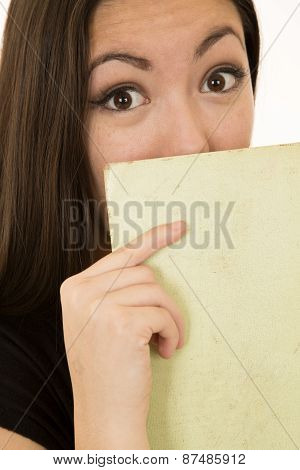 Surpoesed Expression From Female Student Holding Book In Front Of Her Face