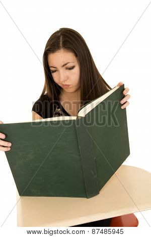 Female Student Reading A Large Book With A Confused Expression