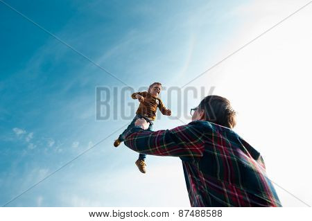 man throws the boy in the sky
