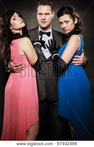 Man In Suit Holding Two Elegant Women Waist.
