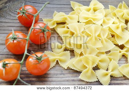 Bunch of small red cherry tomatoes and butterfly shaped pasta farfalle on wooden table