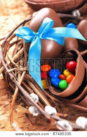 Chocolate Easter eggs in wicker nest, closeup