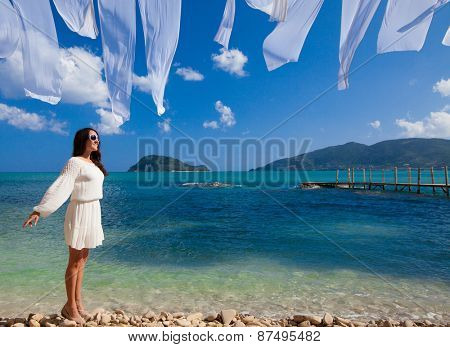 Happy woman in summer white dress on beach. Caucasian girl relaxing and enjoying peace on vacation.