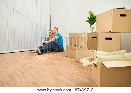 Young Couple Sitting On Floor In New House