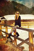 image of balustrade  - beautiful young blonde lady posing on a wooden balustrade in a snowy winter landscape - JPG