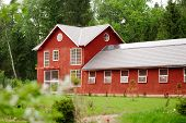 picture of red barn  - beautiful red horse barn among the green forest - JPG