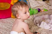 foto of baby diapers  - Cute blonde baby girl with beautiful blue eyes sits on bed in diapers with toy - JPG