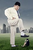 stock photo of stomp  - Business competition concept with big businessman trampling female worker - JPG