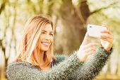 pic of selfie  - Fashionable young Caucasian blonde woman smiling taking a selfie using smart phone outdoors in park on sunny spring day - JPG