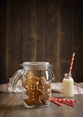 image of gingerbread man  - Gingerbread men in cookie jar with milk and straws in the background - JPG