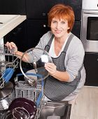 picture of dishwasher  - Woman folding the dishes in the dishwasher - JPG