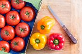 stock photo of yellow-pepper  - Fresh Red Tomatoes Tomatoes and Bell Peppers in Yellow and Red on Top of Wooden Chopping Board with Kitchen Knife - JPG
